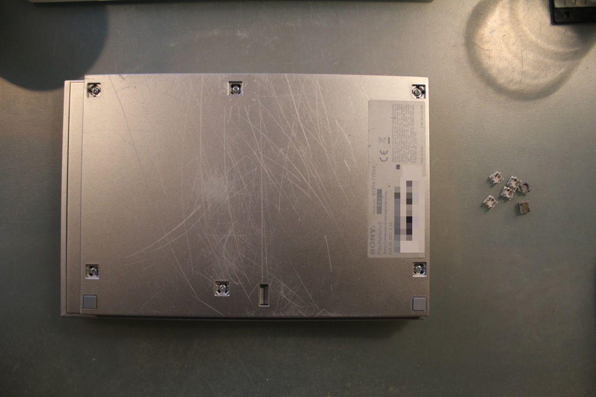 Auf dem Foto ist die Vorderseite der PS2 am unterem Bildrand. Ihr könnt überall die Kappen für die Schrauben abnehmen, indem ihr einen Schlitzschraubenzieher oder euren Fingernagel benutzt. Nur die beiden Gummiquadrate auf der Seite der Front lassen sich nicht abnehmen.